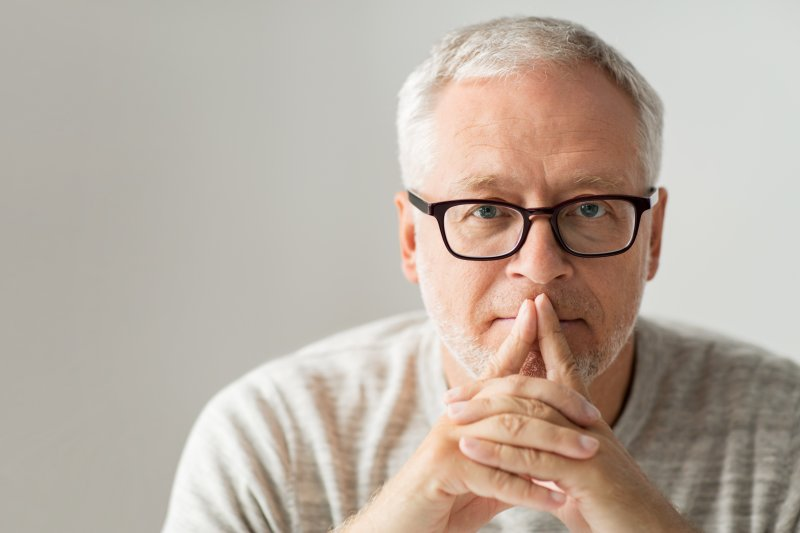 Man with glasses and fingers on his mouth